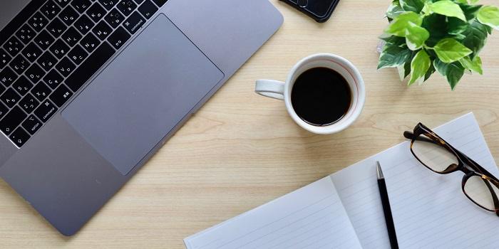 テーブルの上にパソコン、ノート、ボールペン、ブラックコーヒー、眼鏡、観葉植物、スマートフォン